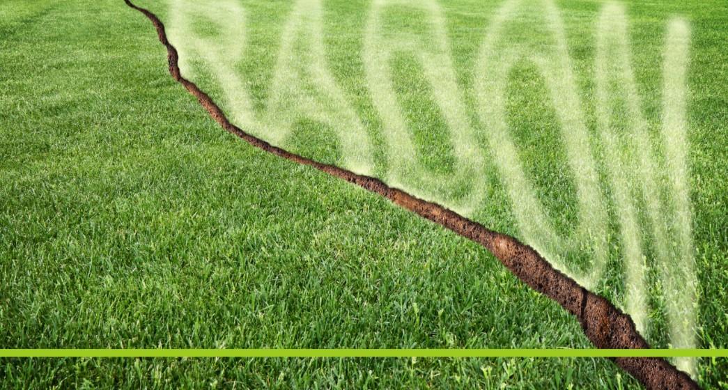 Rasen mit einem diagonalen Riss, aus dem Radongas entweicht, Credit: Canva
