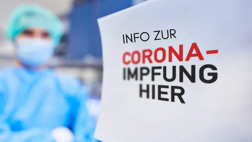 Frau mit Schutzanzug und Maske, Text: Info zur Corona-Impfung hier, Credit: Canva