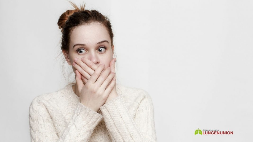 Ein junges Mädchen mit großen Augen bedeckte ihren Mund mit den Händen und sah erschrocken zur Seite. Nahansicht. Credit: Canva