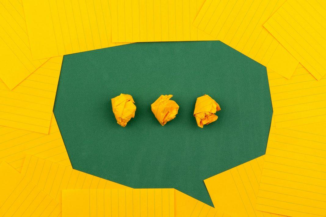 orangefarbene Blätter liegen auf einer grünen Tafel und bilden mit drei zerknitterten Papieren eine Chatblase. Foto: Volodymyr Hryshchenk, Unsplash